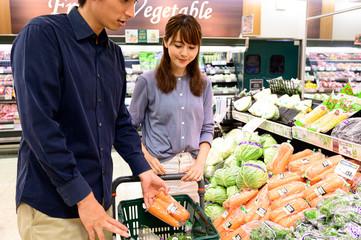 野菜をかごに入れる夫婦