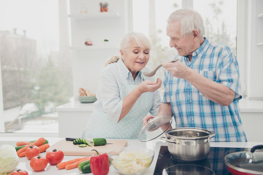 Portrait of lovely nice couple hold hand wooden spoon try soup lunch table cucumber tomato big room indoors