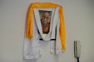 A photograph of the Dalai Lama is seen on the wall of the office of Richard Moore, CEO of Children in the Crossfire, during an interview in Londonderry, Northern Ireland