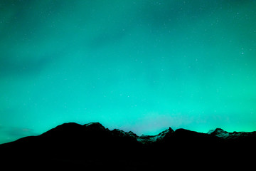 Night sky covered in northern ligths. Turquoise green aurora above dark mountain tops with snow.