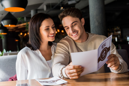 happy man and woman looking at menu in restaurant