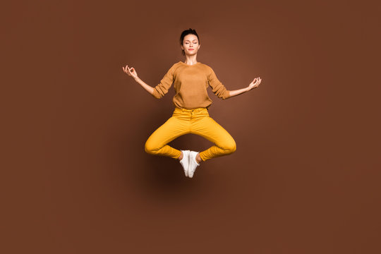 Full length body size photo of jumping concentrated girlfriend having torn away from this world lost in dreams meditating clearing her chakra isolated over brown color pastel background