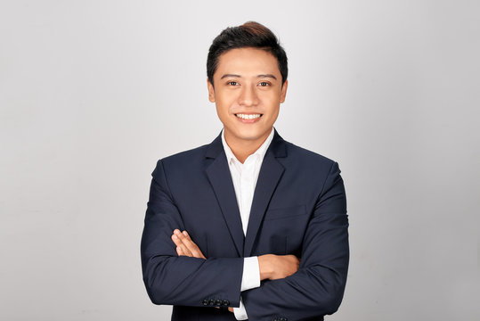 Happy Asian young businessman standing cross-armed on white background