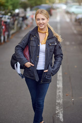 Portrait of young blond woman in city street, holding hands in her casual black unzipped jacket, looking at camera and smiling