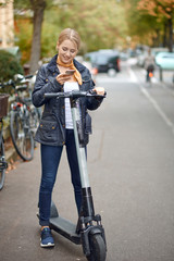 Young woman with electric kick scooter in the street of the city, looking at her phone and smiling. Public transportation renting service, modern urban ecological zero emission transport concept.