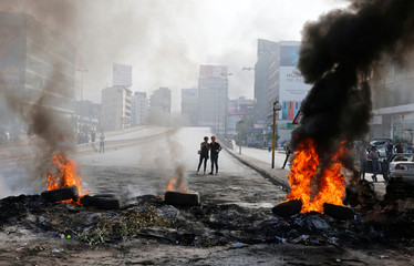 People take pictures of burning tires during a protest over deteriorating economic situation, in Dora