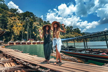 Two beautiful cheerful girls with vietnamese hats on tropical background