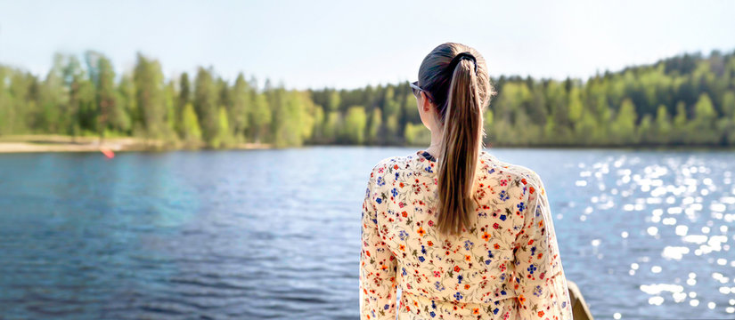 Finnish woman standing and looking at a lake in Finland. Happy person relaxing and enjoying sunny summer vacation or weekend in nature. Back view of carefree lady in dress. Wide banner.