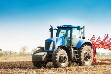 The tractor plows the field, cultivates the soil for sowing grain. The concept of agriculture and agricultural machinery.