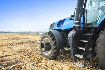 Wall Mural - Modern tractor in the field during planting. The concept of agricultural industry. Copy space.
