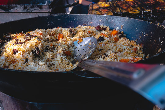 The preparation of traditional Uzbek pilaf with meat, carrots, garlic and spices. Shallow depth of field close view, beautiful and tasty in a large pan, selective focus space for text