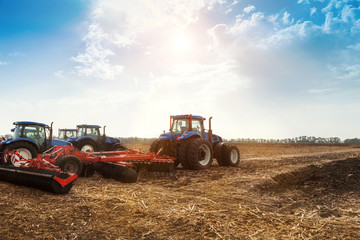 Wall Mural - Several tractors plows the field, cultivates the soil for sowing grain. The concept of agriculture and agricultural machinery.