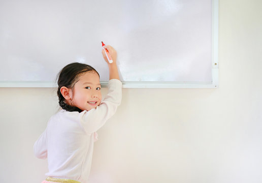 Portrait of happy little Asian child girl or Schoolgirl writing something on whiteboard with a marker and looking at camera in the classroom. White board with copy space for text.
