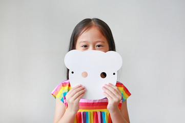 Adorable little child girl holding blank white animal paper mask fronting her face on white background. Idea and concept for kid dressed up playing animal face.