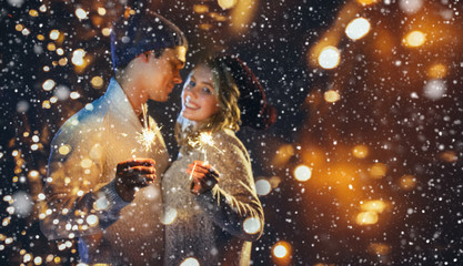 A couple celebrates Christmas together with lights in beautiful snowfall