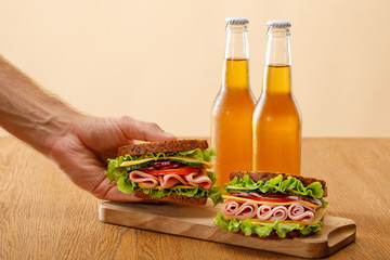 cropped view of man holding fresh sandwich with lettuce, ham, cheese, bacon and tomato near bottles of beer at wooden table isolated on beige