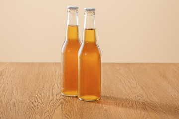 bottles of beer at wooden table isolated on beige