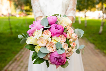 Beautiful wedding bouquet of flowers in the hands of the bride