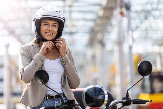 Woman on scooter tightens helmet
