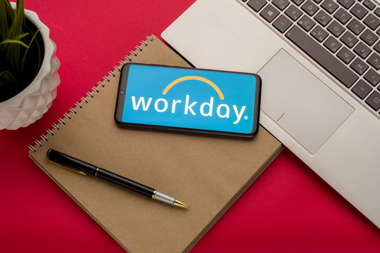 Tula, Russia - october 19, 2019: Workday displayed on a smartphone near modern laptop on red background