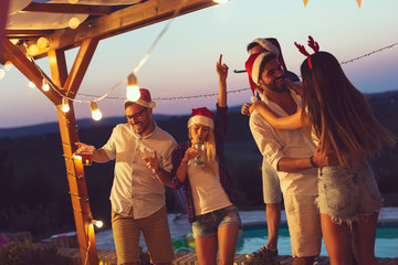Friends dancing at poolside New Years Eve party