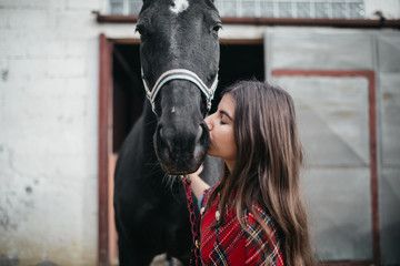 Girl kisses her pet  horse at the stables
