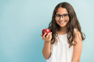 Cute Girl With Healthy Fruit Standing Against Plain Background
