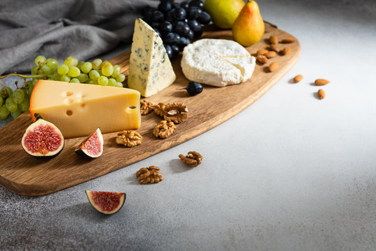 Camembert, brie, blue cheese, maasdam, grapes, pear, figs and nuts on a wooden board on gray background. Side view, copy space. For banner, menu. Healthy food, nutrition concept