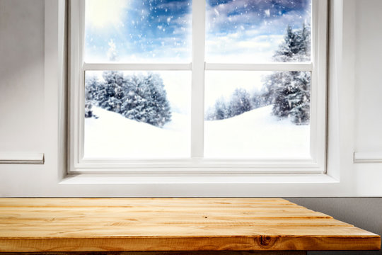 Table background of free space and blurred winter window