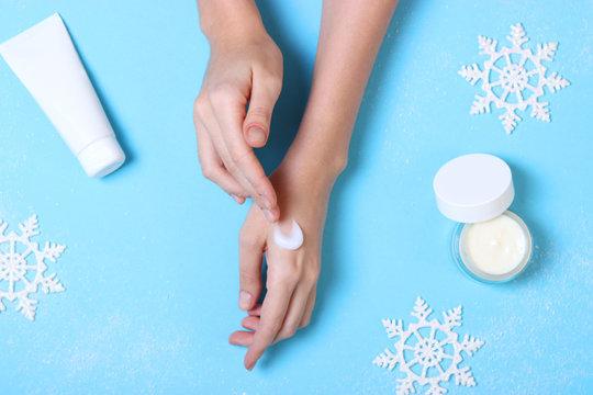 The girl uses cream. Winter hand skin care.