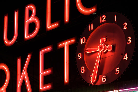 Neon letters and clock, close up. The neon is bright red against a black background.  The sign is located at Pike Place Market, Seattle
