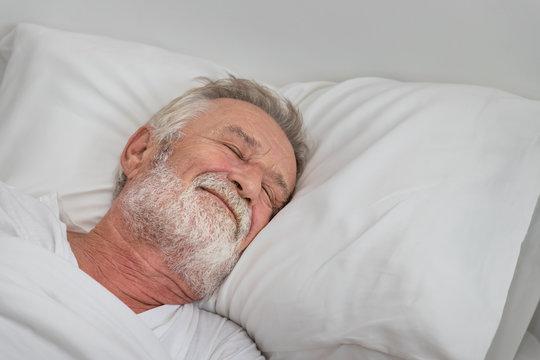 Senior elderly man sleeping peacefully with white blanket in bedroom