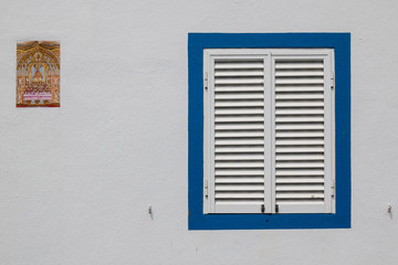 Window with a closed shutter and a religious tile