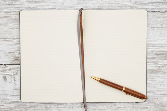 Blank brown journal with pen on a weathered whitewash wood background
