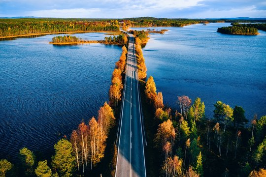 Aerial view of bridge across blue lakes in colorful autumn forest in Finland.
