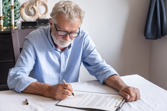 Senior old man elderly examining and signing last will and testament; document is mock-up.