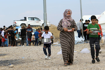 Syrian displaced families, who fled violence after the Turkish offensive in Syria, get food from Barzani charity at a refugee camp in Bardarash on the outskirts of Dohuk