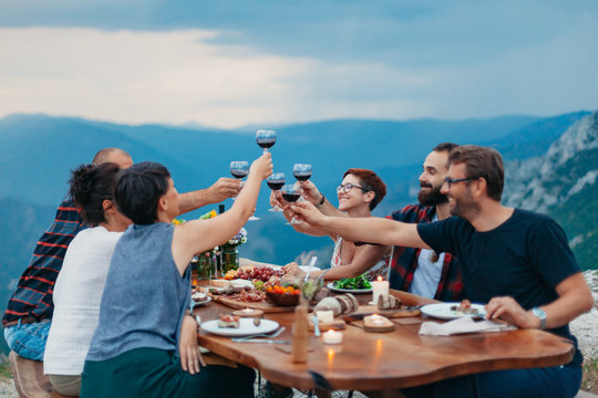 Friends and family gathered for picnic dinner for Thanksgiving. Festive young people celebrating life with red wine, grapes, cheese platter, and a selection of cold meats