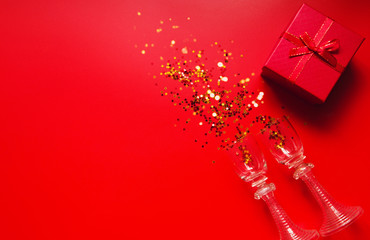 Red background with decorative metallic stars, two vintage glasses and red gift box. Holiday theme backdrop. Festive and party concept