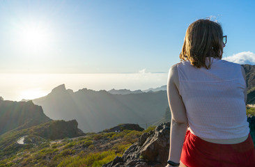 Poster Ontspanning Blond woman sitting with contemplation, enjoying the moment on the sunset in the mountain, relaxing and dreaming. Adolescent girl looking to the horizon alone with casual clothes from the back