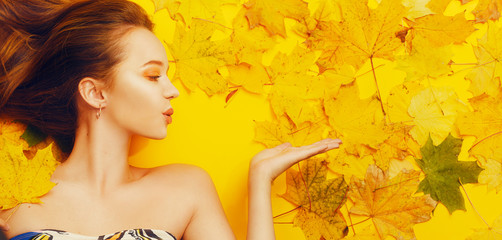Autumn magical girl. The girl sends a kiss, blows in the direction. Happy girl, fall discounts, bright autumn photo. Autumn yellow / orange make-up. Gold earrings. The girl lies in the leaves Wall mural