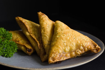 Samosas a spicy blend of vegetables or meat wrapped in a deep fried triangular pastry parcel a popular snack in the Middle East and South Asia
