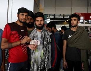 Indian men, who according to local media were deported from Mexico, show a 500 Mexican Pesos banknote after landing in New Delhi