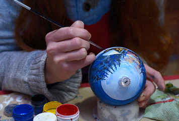 Making Christmas decorations. Decorator's hand painting on a Christmas decoration, sitting at the worktable