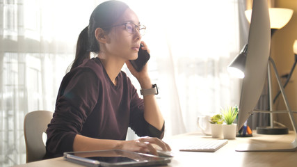 Asian Woman talking on phone while using Computer desktop pc at home, Support her Customer at home
