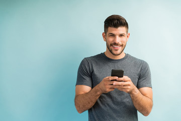 Handsome Man Texting On Smartphone Against Turquoise Background