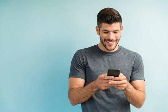 Attractive Hispanic Male Surfing On Mobile Phone