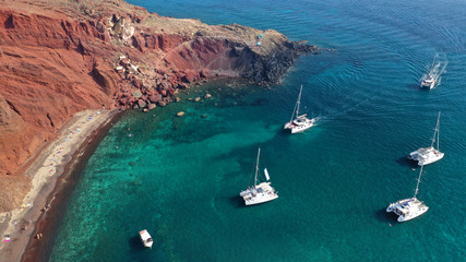 Foto auf Leinwand Santorini Aerial drone photo of iconic famous red rocky volcanic beach with deep turquoise sea visited by sail boats, Santorini island, Cyclades, Greece