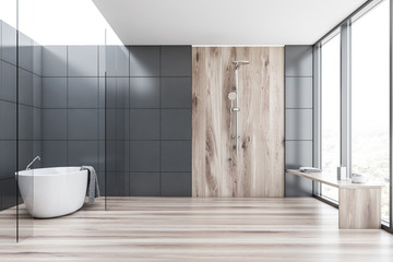 Gray tile and wood bathroom with tub and shower