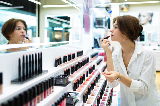 Young woman puts on red lipstick at cosmetics shop